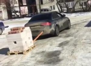 На видео сняли, как Audi тянет за собой сотню кирпичей в Воронеже